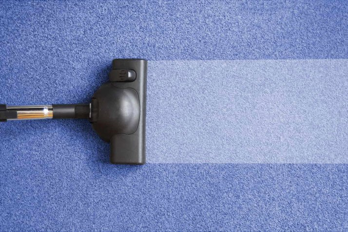 Vaccum cleaner head passing over carpet and leaving it clean